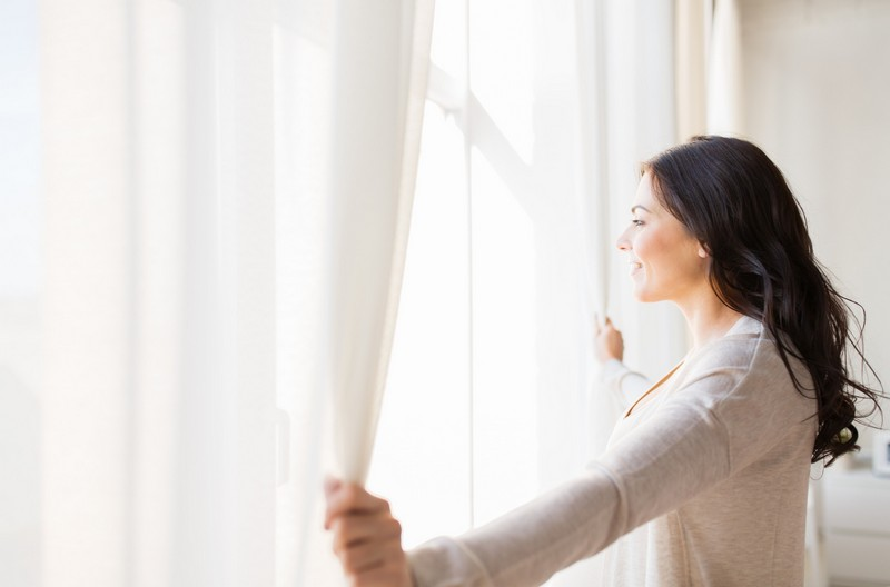 close up of woman opening window curtains