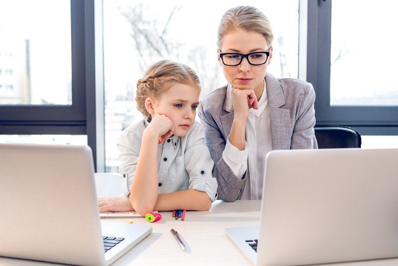 mother and daughter talking while sitting at table with laptops in office